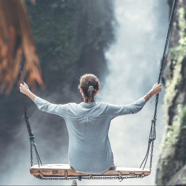une femme se balance devant une cascade